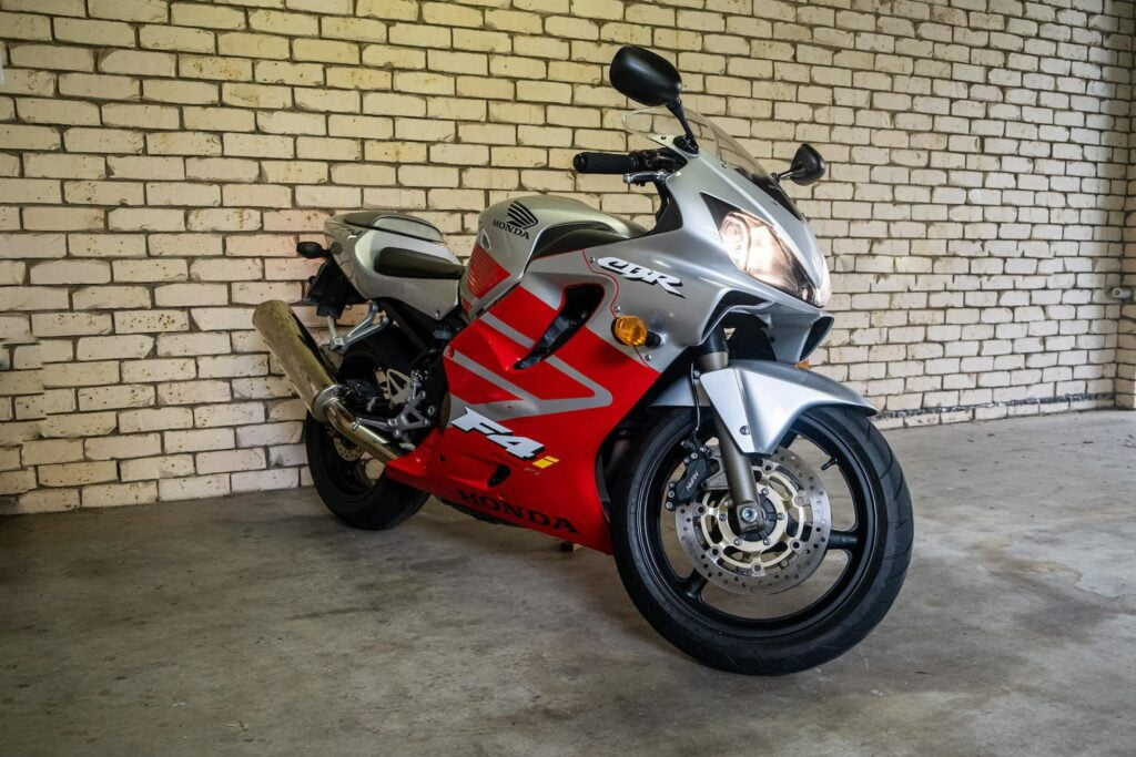 Photo of my CBR600F4i against a brick wall with headlights on