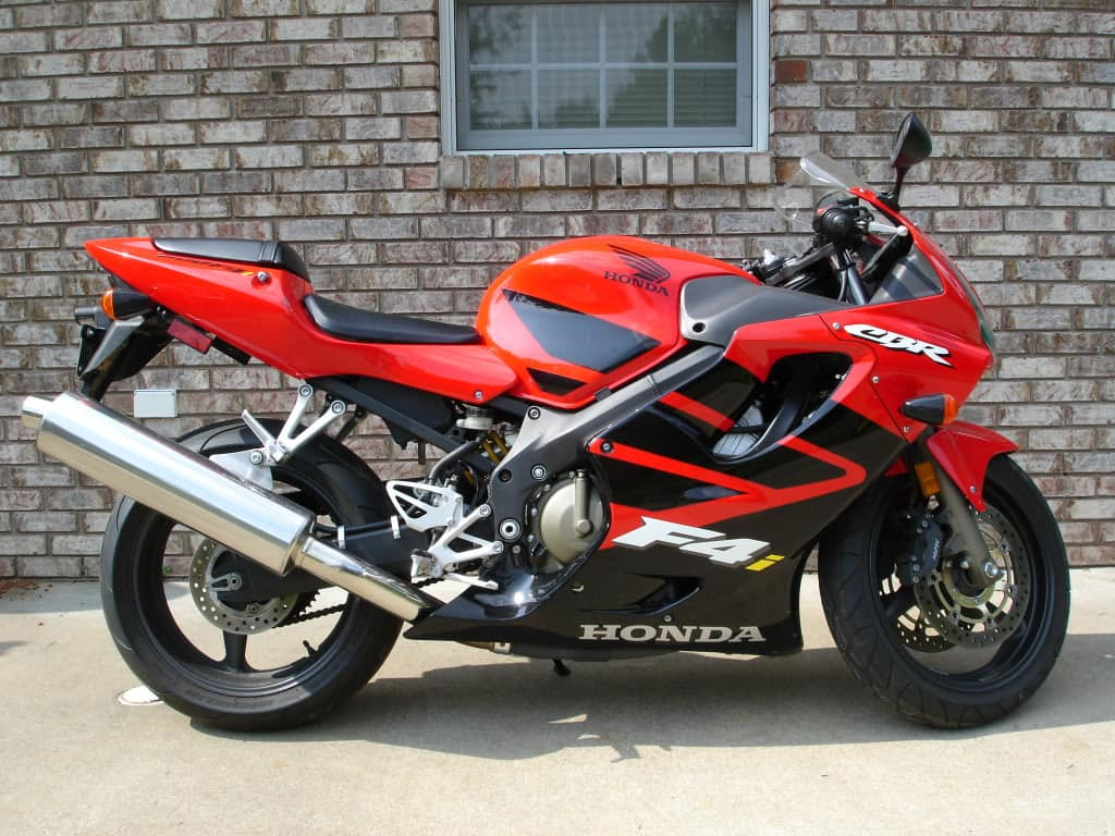 Red and black Honda CBR600F4i against brick wall