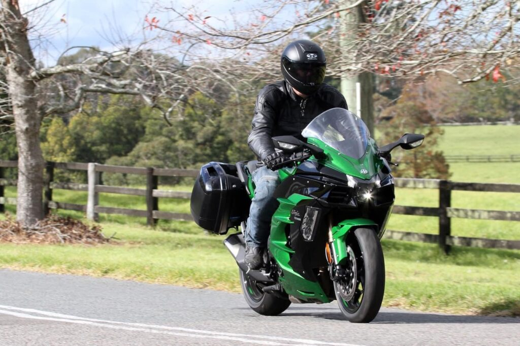Riding position of the 2018 Ninja H2 - comfortable and upright. Green scenery in background