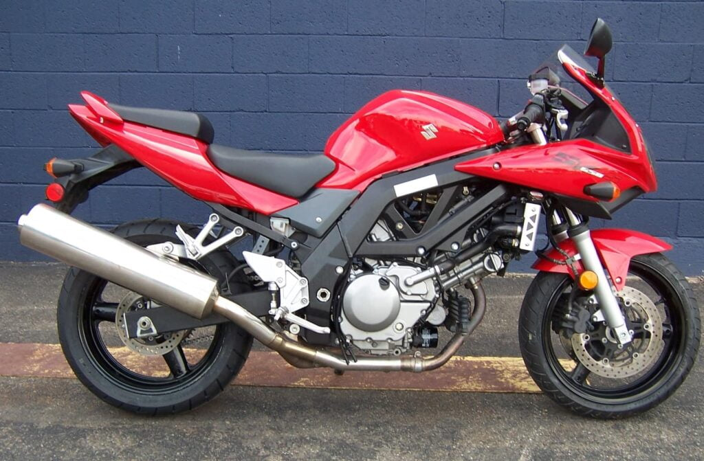 A red SV650S, with bikini fairing, second generation. A great motorcycle to buy used!