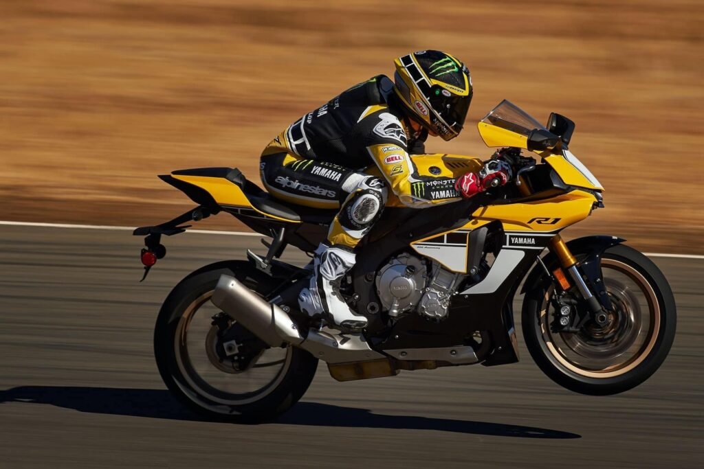 This is a Yamaha R1 racing down a track doing a small wheelie part of a guide to buying a used Yamaha R1.