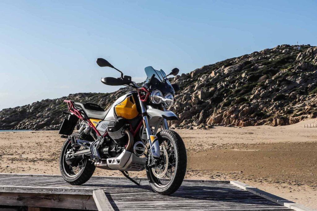Moto Guzzi V85 TT on boardwalk hill in background Giallo Sahara - air cooled